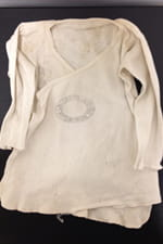A child's shirt from 1951 – the shirt is accompanied by a story by its owner's mother of how her daughter recovered from pneumonia thanks to the care she received at Children's.