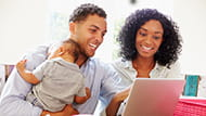 African American couple holding a baby looking at a lap top