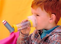 Boy with asthma using an inhaler
