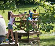 Boy holding a fish and fishing rod